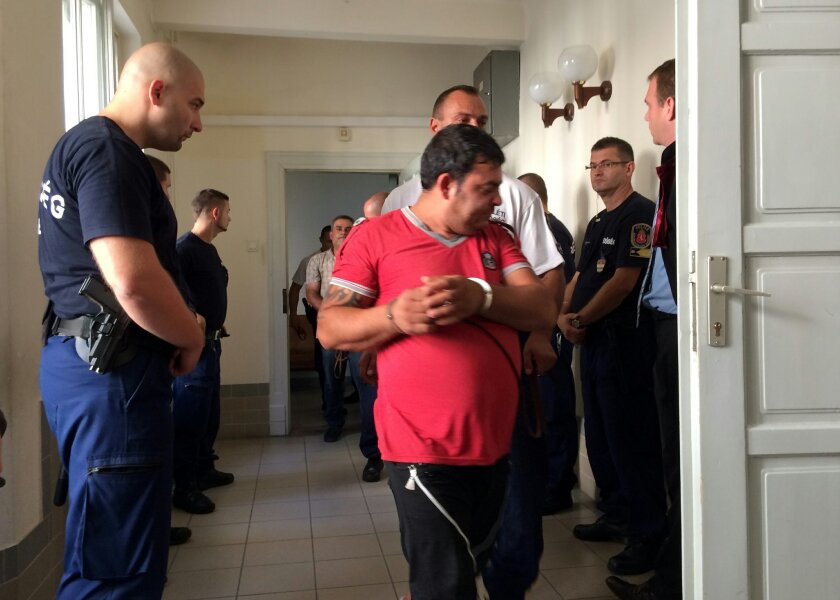 A man, centre, accused of being involved in the trafficking of the 71 migrants found dead in a truck in Austria, is escorted by police officers at a court in Kecskemet, Hungary on Saturday, Aug. 29, 2015. (AP Photo/Pablo Gorondi) HUNGARY OUT