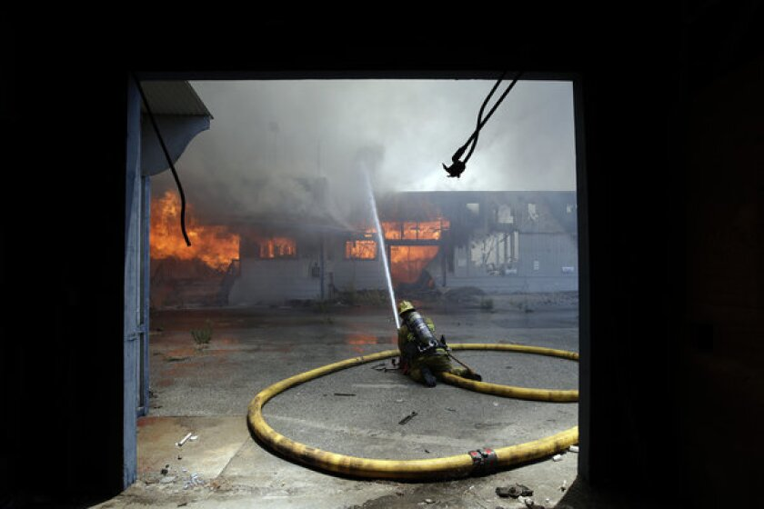A firefighter sprays water on a burning warehouse in City of Industry.