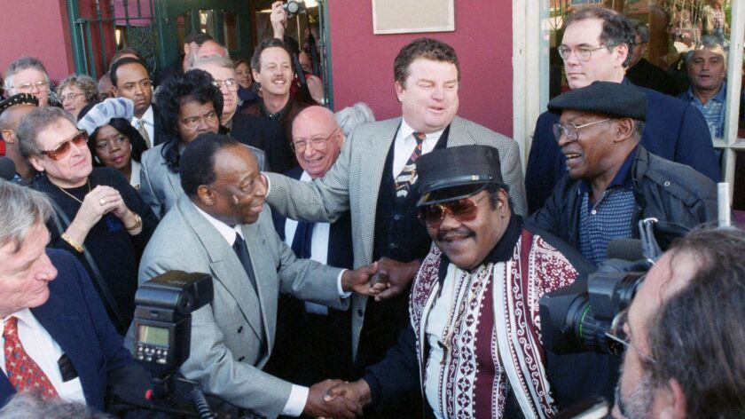 FILE - In a Dec. 10, 1999 file photo, Fats Domino, center right, shakes hands with Dave Bartholomew,
