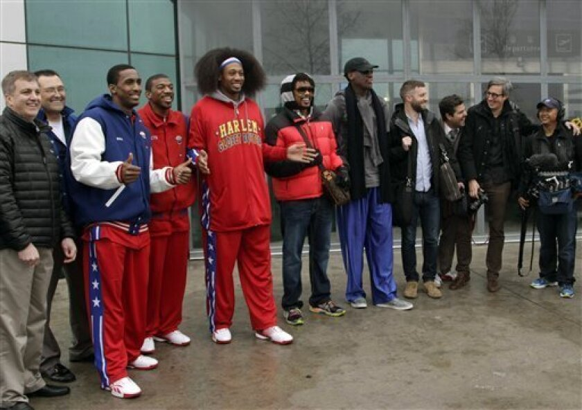"""Flamboyant former NBA star Dennis Rodman, fifth from right, poses with three members of the Harlem Globetrotters basketball team, in red jerseys, and a production crew for the media upon arrival at Pyongyang Airport, North Korea, Tuesday, Feb. 26, 2013. Rodman known as """"The Worm"""" arrived in Pyongya"""