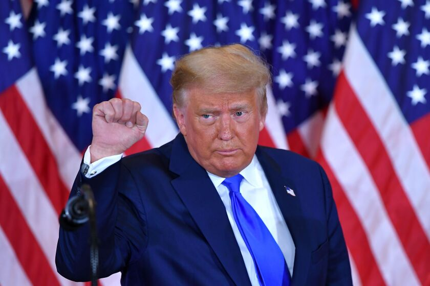 President Trump pumps his fist after falsely claiming election fraud during an election night speech in the White House.