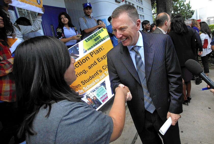 LAUSD Supt. John Deasy shakes hands with Manual Arts High School seniorLaura Aguilar, 17 after the district announced a new program in which school police will no longer issue citations for minor offenses.