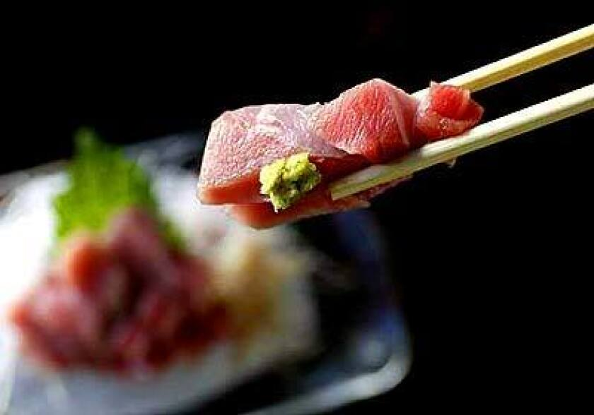 It's customary to pick up sashimi, like this toro (fatty tuna belly), with chopsticks, then add wasabi to taste.