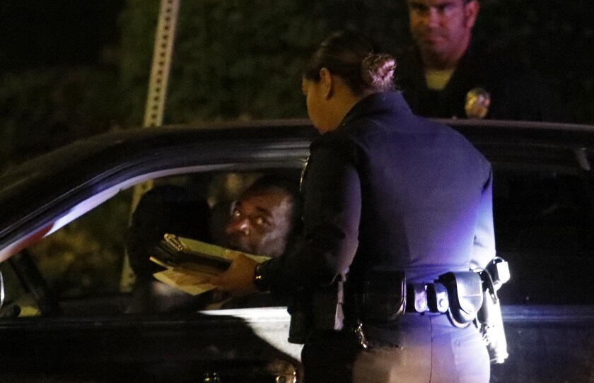 LAPD officers give a man a ticket for an expired registration in South Los Angeles on July 25, 2019.