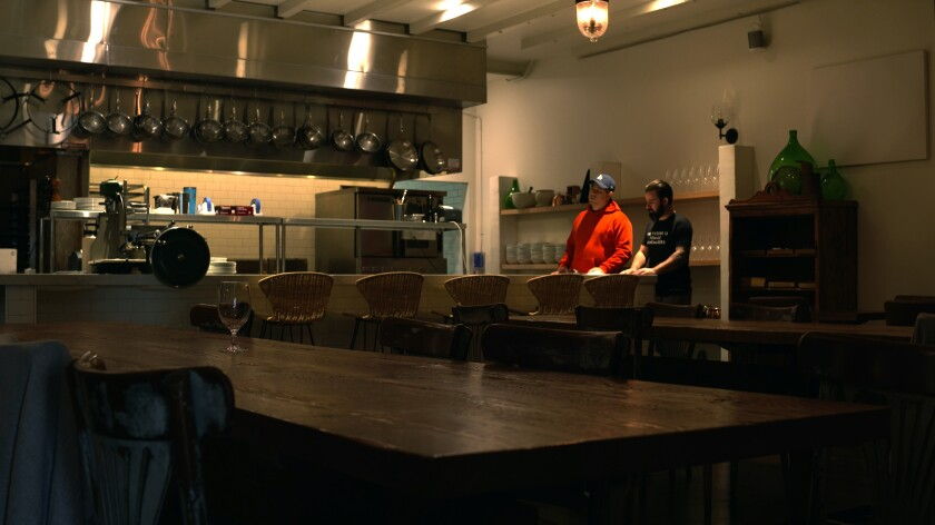 Chef Chad Colby and another man inside the empty Antico restaurant.