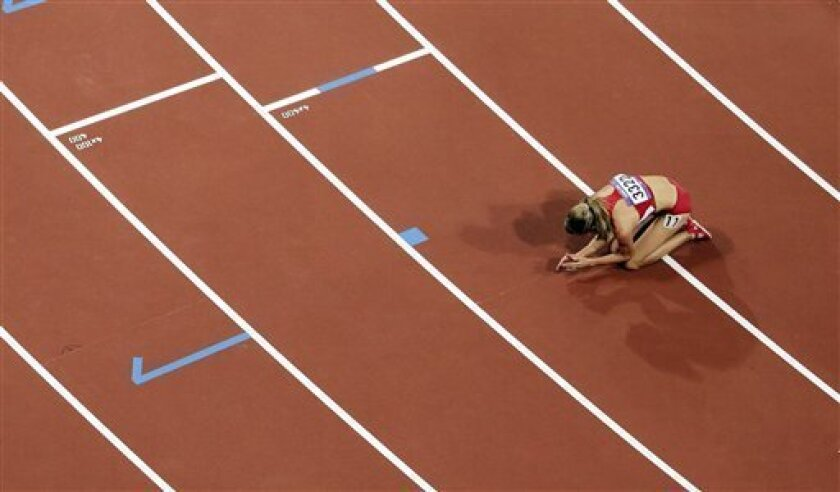 United States' Morgan Uceny lays on the track after falling down on the final lap of the women's 1500-meter during the athletics in the Olympic Stadium at the 2012 Summer Olympics, London, Friday, Aug. 10, 2012. (AP Photo/Morry Gash)