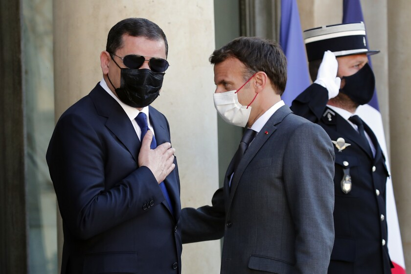 French President Emmanuel Macron, right, greets Libyan Prime Minister Abdulhamid Dbeibeh before their meeting at the Elysee Palace, in Paris, Tuesday, June 1, 2021. (AP Photo/Francois Mori)