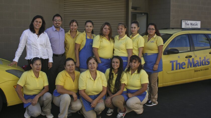 Manager Erik Tello poses with 'The Maids' of San Diego staff.