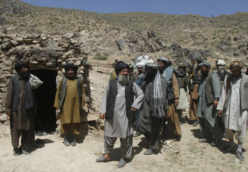 In this Friday, May 27, 2016 photo, Senior leader of a breakaway faction of the Taliban Mullah Abdul Manan Niazi, third left, arrives to give a speech to his fighters, in Shindand district of Herat province, Afghanistan. In the rugged terrain of the Taliban heartland in southern Afghanistan, the fi