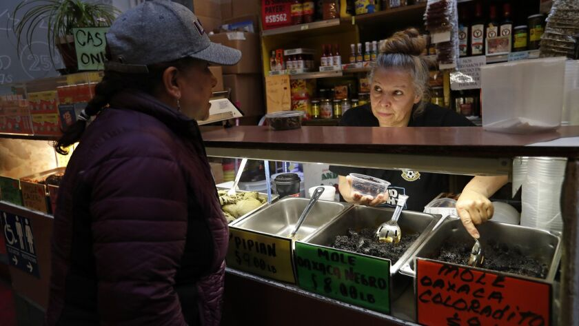 Sonia Solas, left, orders a container of mole from vendor Rocio Lopez inside the Grand Central Market.