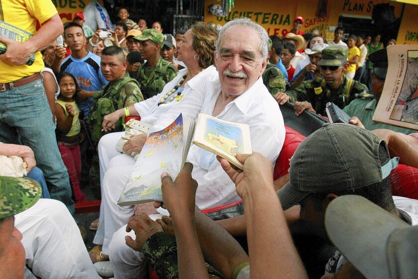 Gabriel Garcia Marquez, sitting with his wife, Mercedes Barcha, is asked by admirers in May 2007 to dedicate their books before boarding the train to visit his hometown of Aracataca, Colombia, for the first time in 20 years.