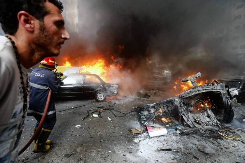 A man walks past as a firefighter works to extinguish the blaze at the site of a car bombing in south Beirut.