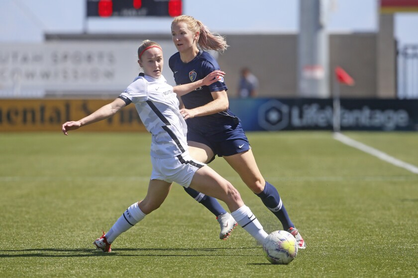 North Carolina Courage's Samantha Mewis, rear, passes the ball as Portland Thorns FC forward Tyler Lussi, left, defends during the first half of an NWSL Challenge Cup soccer match at Zions Bank Stadium Friday, July 17, 2020, in Herriman, Utah. (AP Photo/Rick Bowmer)