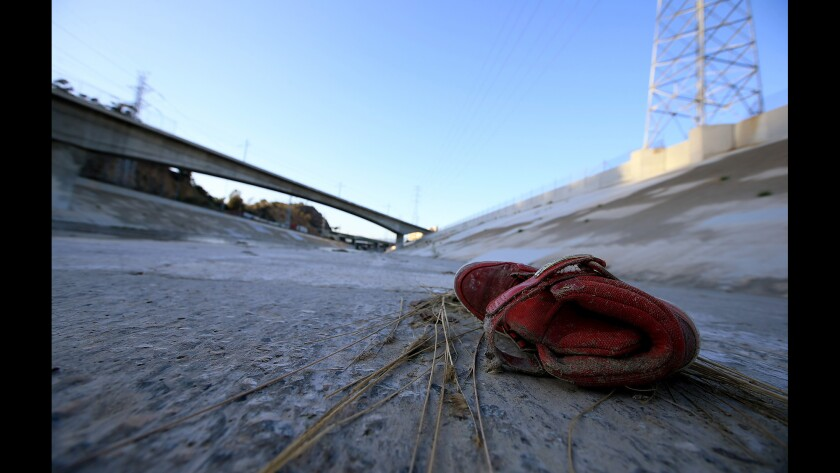 An old red sneaker rests in the bed of the Los Angles River.