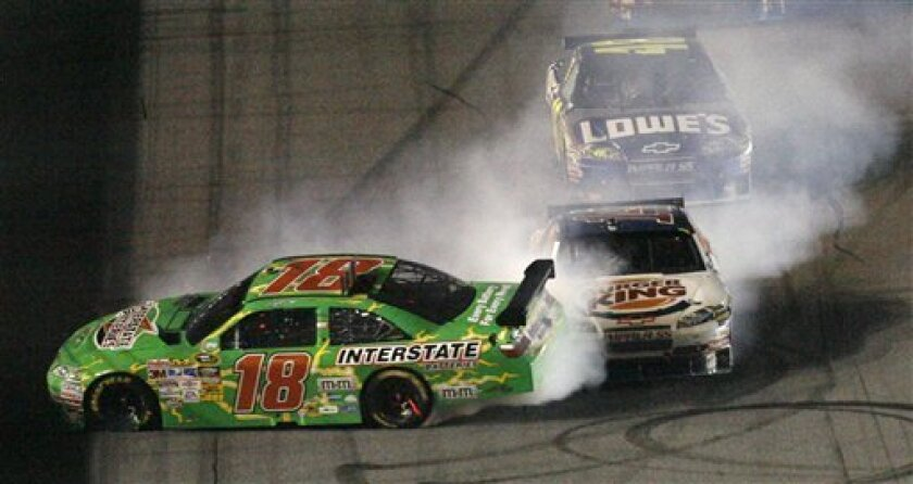 Kyle Busch spins as he is hit by Tony Stewart heading to the finish line in the Coke Zero 400 auto race at Daytona International Speedway in Daytona Beach, Fla., Saturday, July 4, 2009. Tony Stewart won the race and Busch finished 14th. (AP Photo/Glenn Smith)