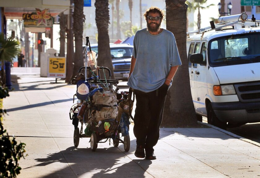 A homeless man tows his belongings behind him as he walks east on Pier View Way in downtown Oceanside in 2015.