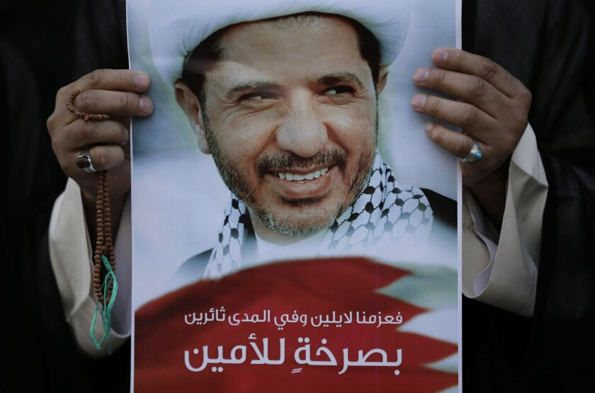 FILE - In this Wednesday, Feb. 25, 2015 file photo, a Bahraini anti-government protester holds up an image of jailed Shiite opposition leader Sheikh Ali Salman demanding his freedom during a protest in Daih, Bahrain.  A Bahraini appeals court has more than doubled the prison term for the country's