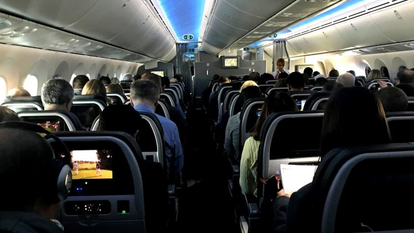 Main cabin passengers pass the time aboard American Airlines flight 2331, a Boeing 787-800 Dreamline