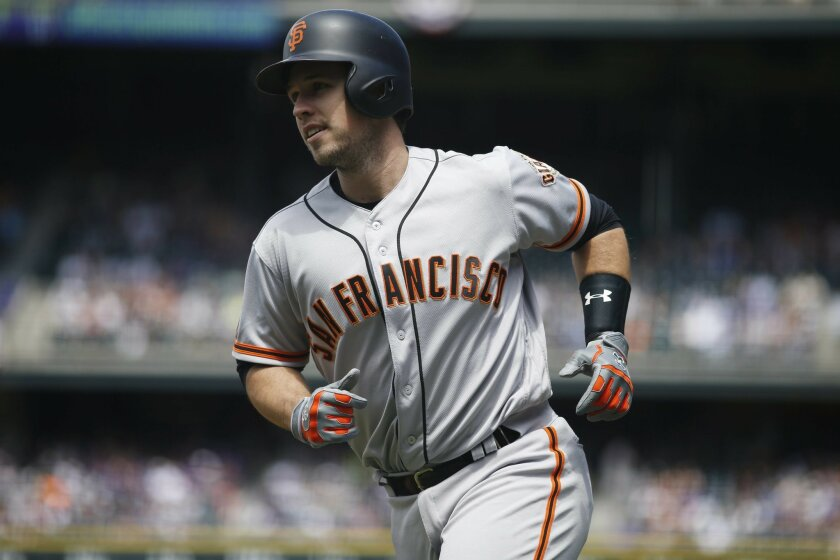 San Francisco Giants' Buster Posey heads back to the dugout after hitting a three-run home run off Colorado Rockies starting pitcher Eddie Butler in the first inning of a baseball game Saturday, May 28, 2016, in Denver. (AP Photo/David Zalubowski)