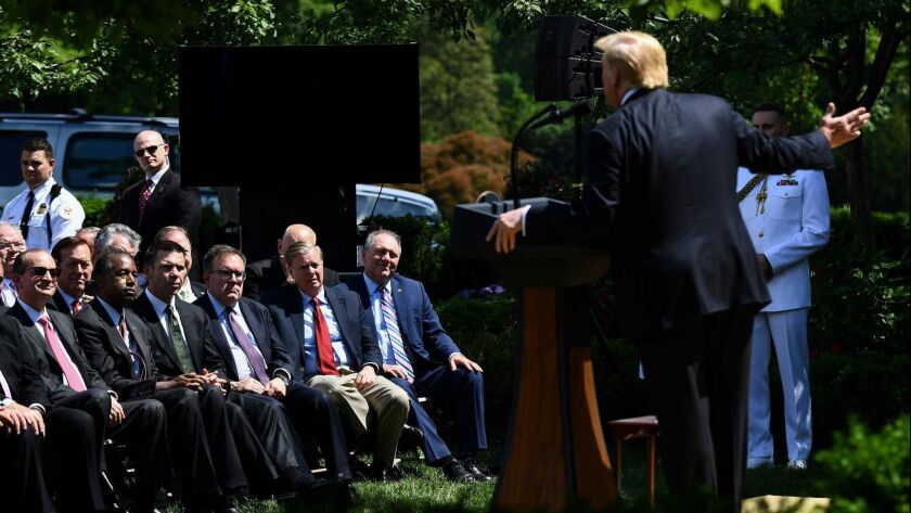 Cabinet members and senators listen to President Trump announce a new immigration proposal in the Rose Garden of the White House on May 16.