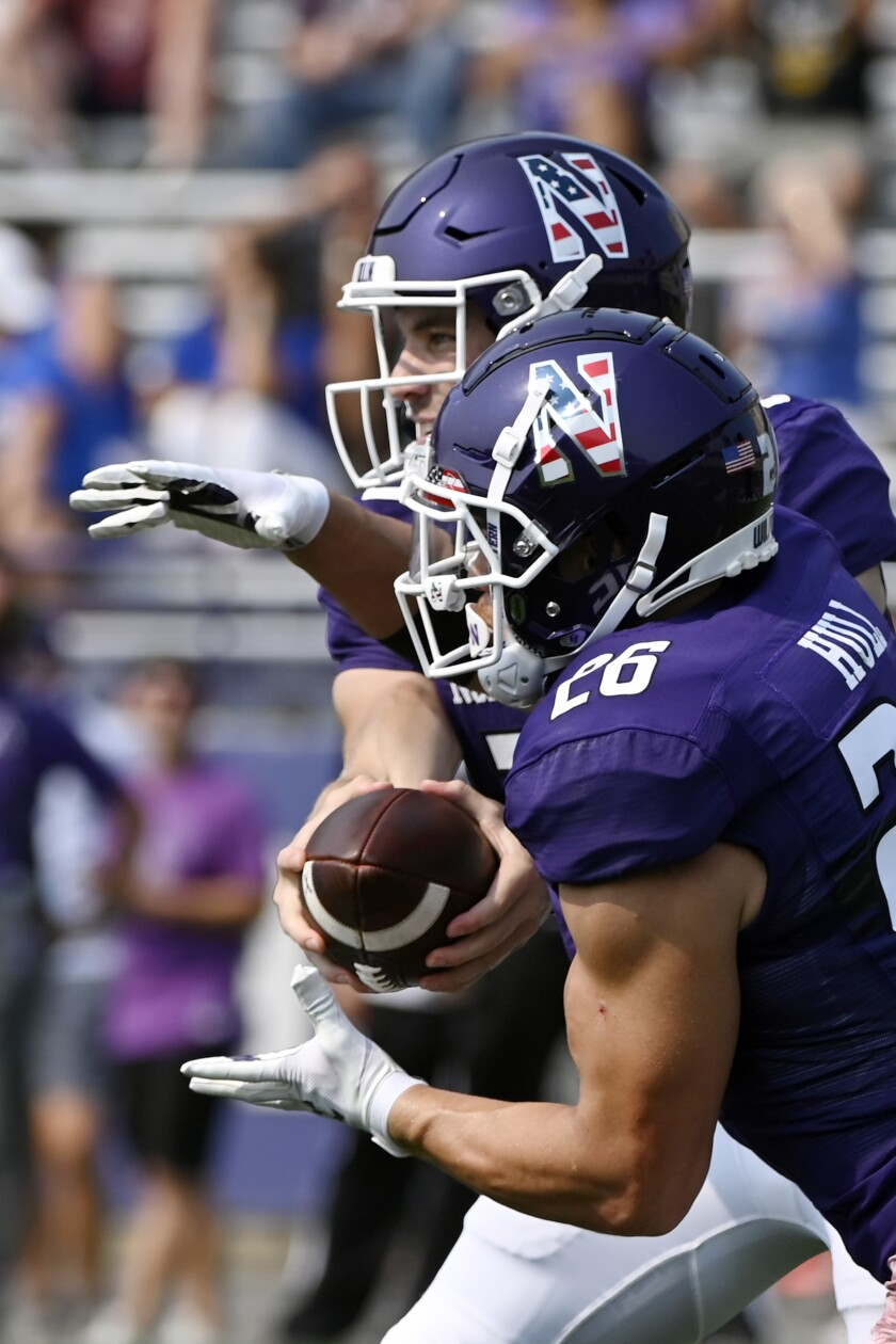 Northwestern quarterback Hunter Johnson, rear, hands the ball off to running back Evan Hull (26) against Indiana State during the first half of an NCAA college football game in Evanston, Ill, Saturday, Sept.11, 2021. (AP Photo/Matt Marton)