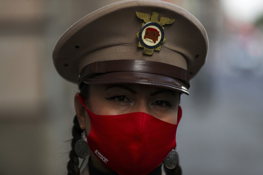 An organ grinder, wearing a protective face mask, eyes the camera as she waits for a delivery of donated groceries, in Mexico City, Thursday, June 4, 2020. CADENA, a non-profit organization dedicated to assisting during emergencies and disasters around the world, dispatched groceries to hundreds of organ grinders who play for tips from passersby but have lost their source of income due to restrictions amid the new coronavirus. (AP Photo/Fernando Llano)