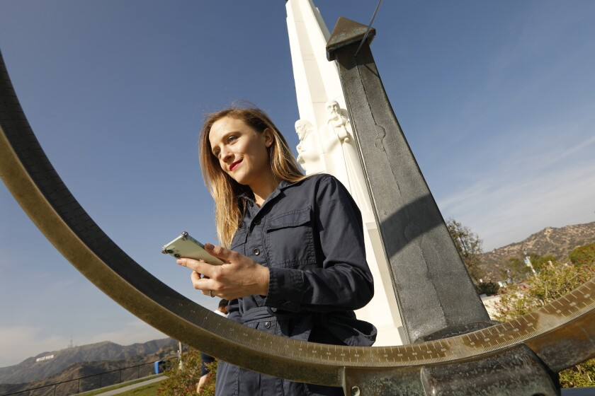 Ellen Reid, outdoors in front of a statue, holds her cellphone.