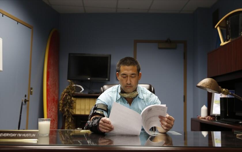 Derek Kawakami reads in his office in Lihue, Hawaii.