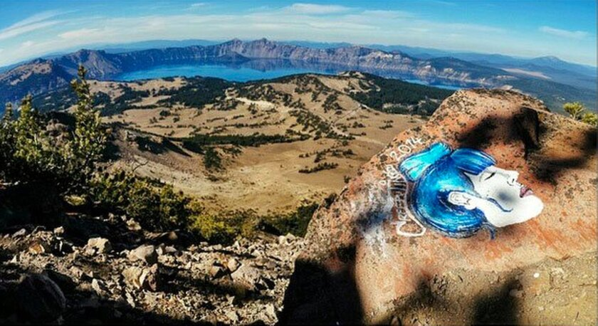 FILE - This undated file photo taken from an Instagram posting shows an overlook of Crater Lake in Oregon with a rock painting. As investigators find more of the eerie faces scrawled on rocks in some of the West's most picturesque landscapes, park managers are trying to figure out how they'll get r