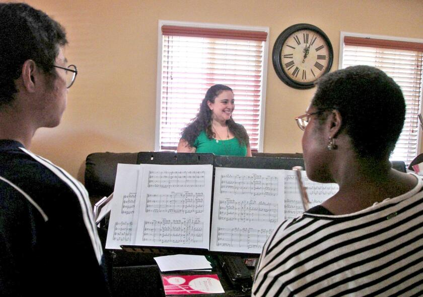 Flute students Han Lee and Debra Nicholas take notes from La Crescenta music teacher Thea Komen during a July 10 rehearsal for an upcoming concert.