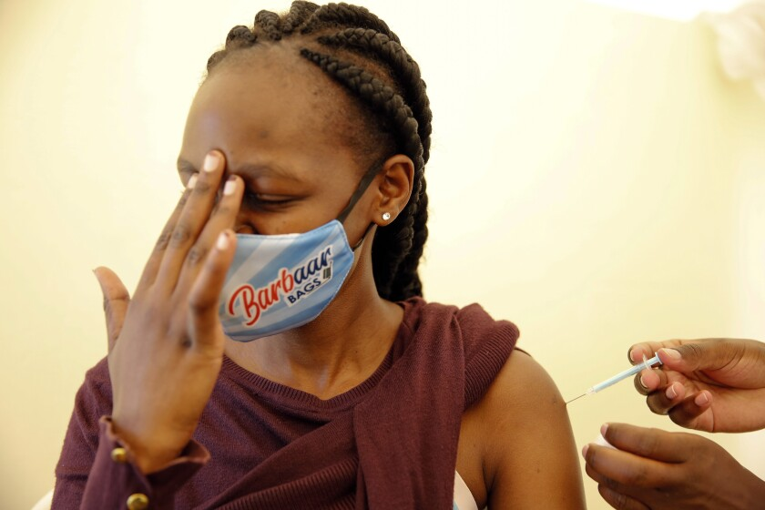 A woman receives a dose of AstraZeneca COVID-19 vaccine manufactured by the Serum Institute of India and provided through the global COVAX initiative, at Kenyatta National Hospital in Nairobi, Thursday, April 8, 2021. (AP Photo/Brian Inganga)