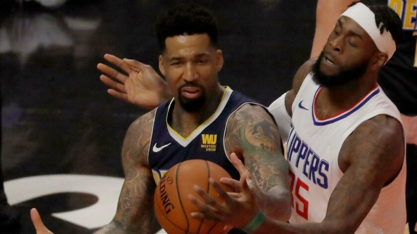 Clippers center Willie Reed, right, defends against Nuggets forward Wilson Chandler in the first quarter on Wednesday at Staples Center.