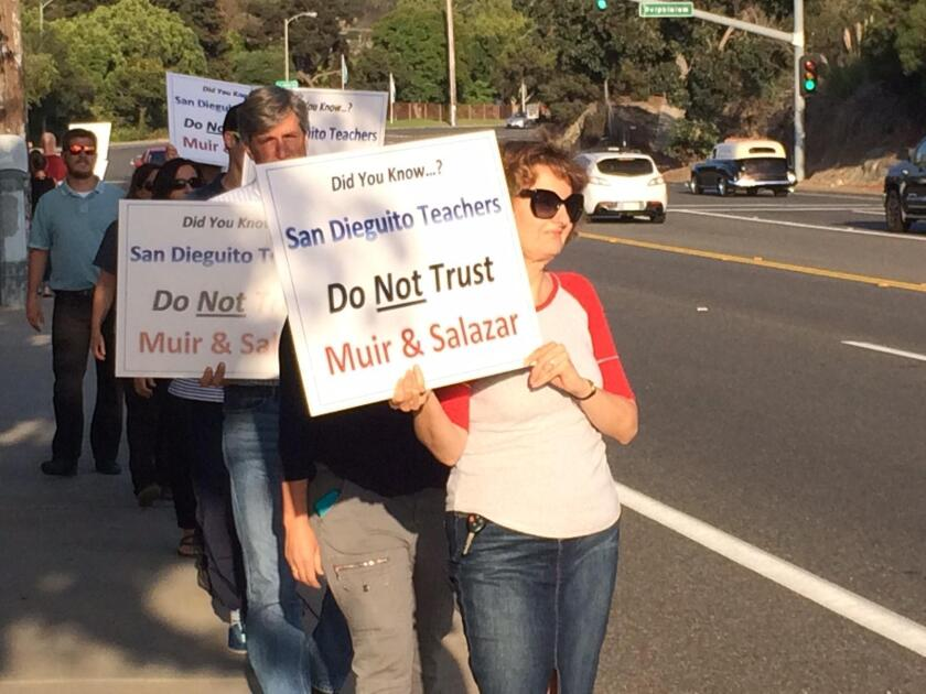 Protesters holding signs Sept. 1 in opposition to board members John Salazar and Mo Muir.