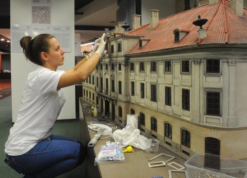 In this Oct. 2, 2014 photo a worker finishes one of the miniature replicas of Warsaw's lost buildings, that were demolished by the Nazis during World War II, in Warsaw, Poland. (AP Photo/Alik Keplicz)
