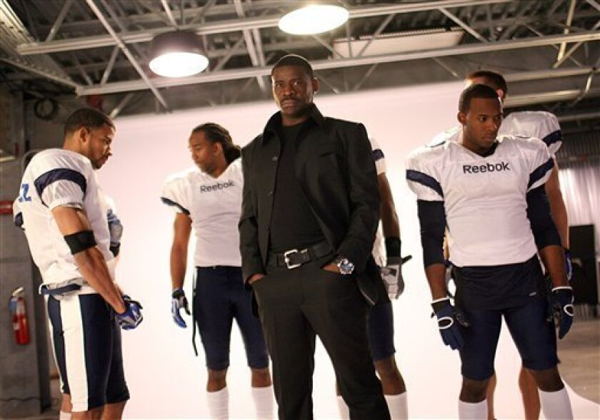 """Cast member Andrew Hawkins (right) poses with NFL Hall of Famer and host Michael Irvin, center, and other cast mates during filming of a new Spike TV series, """"4th and Long,"""" on Wednesday, March 11, 2009 at the Cotton Bowl in Dallas, Texas.  The series gives a football hopeful, such as Hawkins, a sh"""