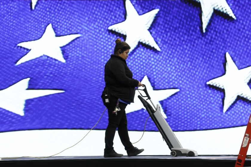 A worker vacuums the stage before the Iowa Democratic Party's Liberty and Justice Celebration, Friday, Nov. 1, 2019, in Des Moines, Iowa. (AP Photo/Charlie Neibergall)