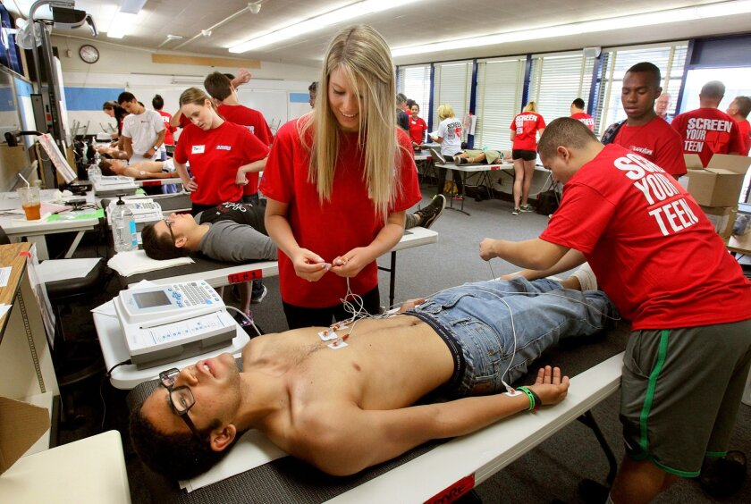 """15 year old track athlete D'Isaac Young, of San Diego, gets connected to an EKG machine for his heart screening by volunteers Amelia Schricker, left, and Jared Ekong, at right, at the """"Screen Your Teen"""" event at Madison High School."""