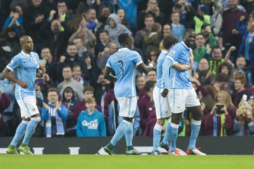 Manchester City's Yaya Toure, right, celebrates with teammates after scoring during the English Premier League soccer match between Manchester City and Norwich at the Etihad Stadium, Manchester, England, Saturday Oct. 31, 2015. (AP Photo/Jon Super)