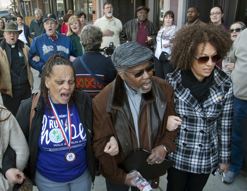 """In this March 6 file photo, from left, Della Montgomery-Riggins, Charles Thornton and Rachel Dolezal link arms and sing """"We Shall Overcome"""" at a rally in downtown Spokane, Wash., responding to a racist and threatening package received by Dolezal, the NAACP president."""
