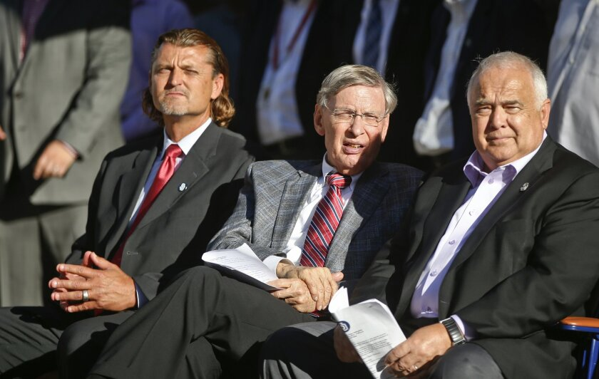 Baseball commissioner Bud Selig, center, sits with San Diego Padres CEO Ron Fowler and former Padres pitcher Trevor Hoffman, left, at a ceremony announcing that part of the Padres' Petco Park is being named Selig Hall of Fame Plaza in honor of the commissioner, who is retiring, Tuesday, Aug. 26, 20