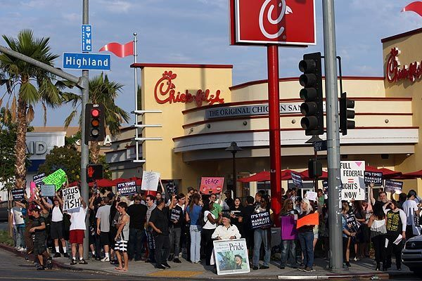 "A group of gay-rights and same-sex marriage supporters protest in front of Chick-fil-A restaurant in Hollywood on Friday. LGBT supporters declared Friday to be National Same Sex Kiss Day and encouraged others to show up at Chick-fil-A restaurants nationwide to stage a ""kiss-in."""