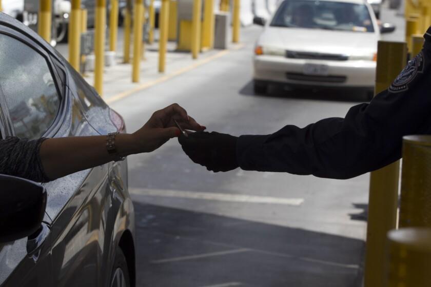 Un agente de la oficina de Aduanas y Protección Fronteriza comprueba la identificación de un conductor