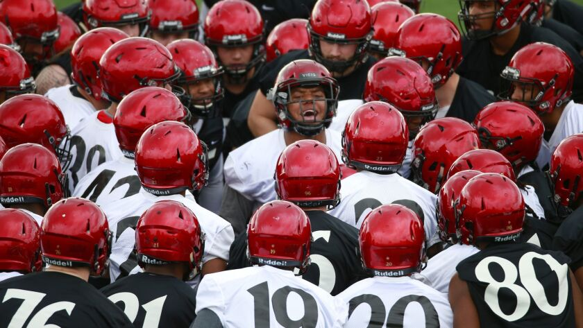 San Diego State linebacker Kyahva Tezino (center) gives his teammates some motivational words Monday before SDSU's first spring practice.