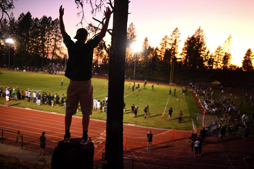 Fans watch the high school football team in Paradise