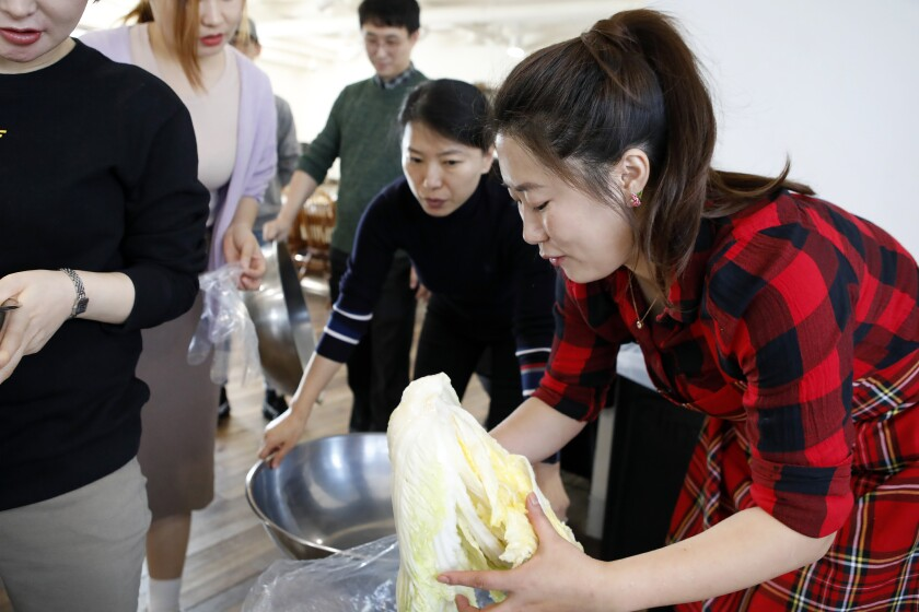 Jessie Kim prepares nappa cabbage marinated in salt water as she teaches North Korean-style kimchi at  her cooking class in Seoul.