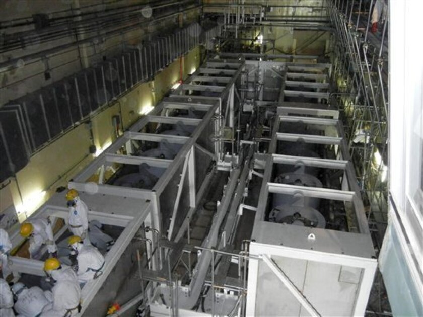 In this June 1, 2011 photo released Saturday, June 4, 2011 by Tokyo Electric Power Co. (TEPCO), workers inspect equipments inside the cesium absorption tower, part of the radioactive water processing facilities at Fukushima Dai-ichi nuclear power plant in Okuma, Fukushima prefecture, northeastern Japan. The Japanese utility battling to bring its radiation-spewing nuclear reactor under control said Sunday, July 5, 2011 that 1,500 more tons of radioactive water are being moved into temporary storage in the processing facilities, the latest attempt to prevent a massive spill of contaminated water into the environment. (AP Photo/Tokyo Electric Power Co.) EDITORIAL USE ONLY