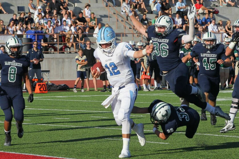 La Costa Canyon defenders James Vanderpool (36) and Cole Yates (33) grasp at air as Newport Beach Corona del Mar quarterback Peter Bush runs into the end zone.