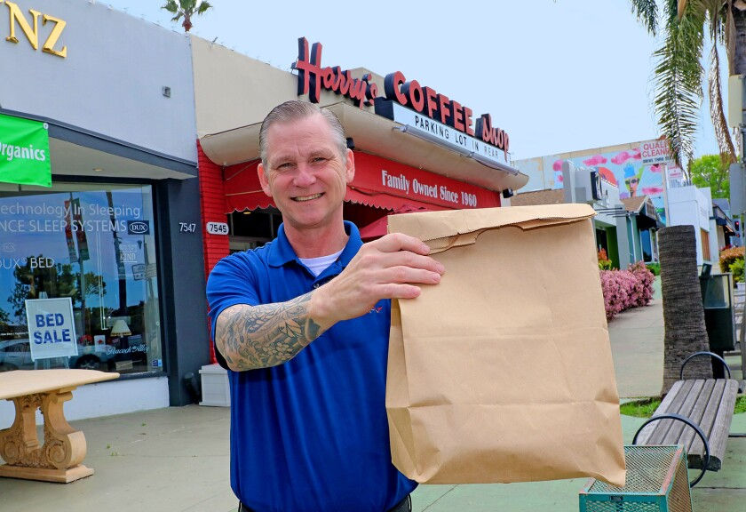 Harry's Coffee Shop manager Tom Frankenberger has an order ready for curbside pickup at the La Jolla diner. He said some of the local hangout's longtime customers still stop by for takeout, but San Diego County's emergency regulations not allowing onsite dining — to help stop the spread of coronavirus — has put a major dent in business.