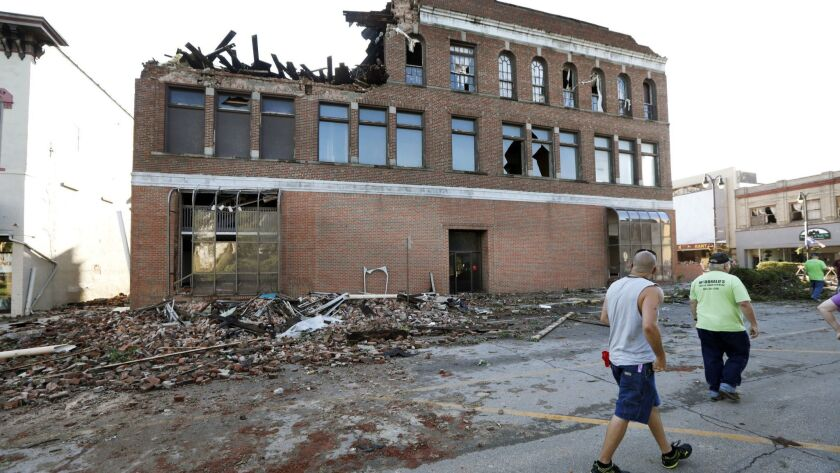 Local residents walk past a tornado damaged building on Main Street, Thursday, July 19, 2018, in Mar