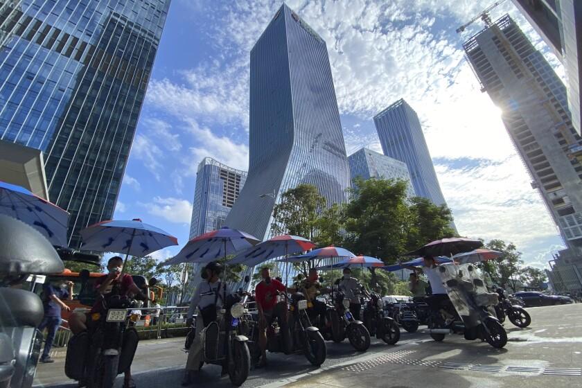 Hombres en bicicletas eléctricas esperan por pasajeros delante de las oficinas centrales del promotor inmobiliario Evergrande Group en Shenzhen, China, el 24 de septiembre del 2021. (AP Foto/Ng Han Guan)